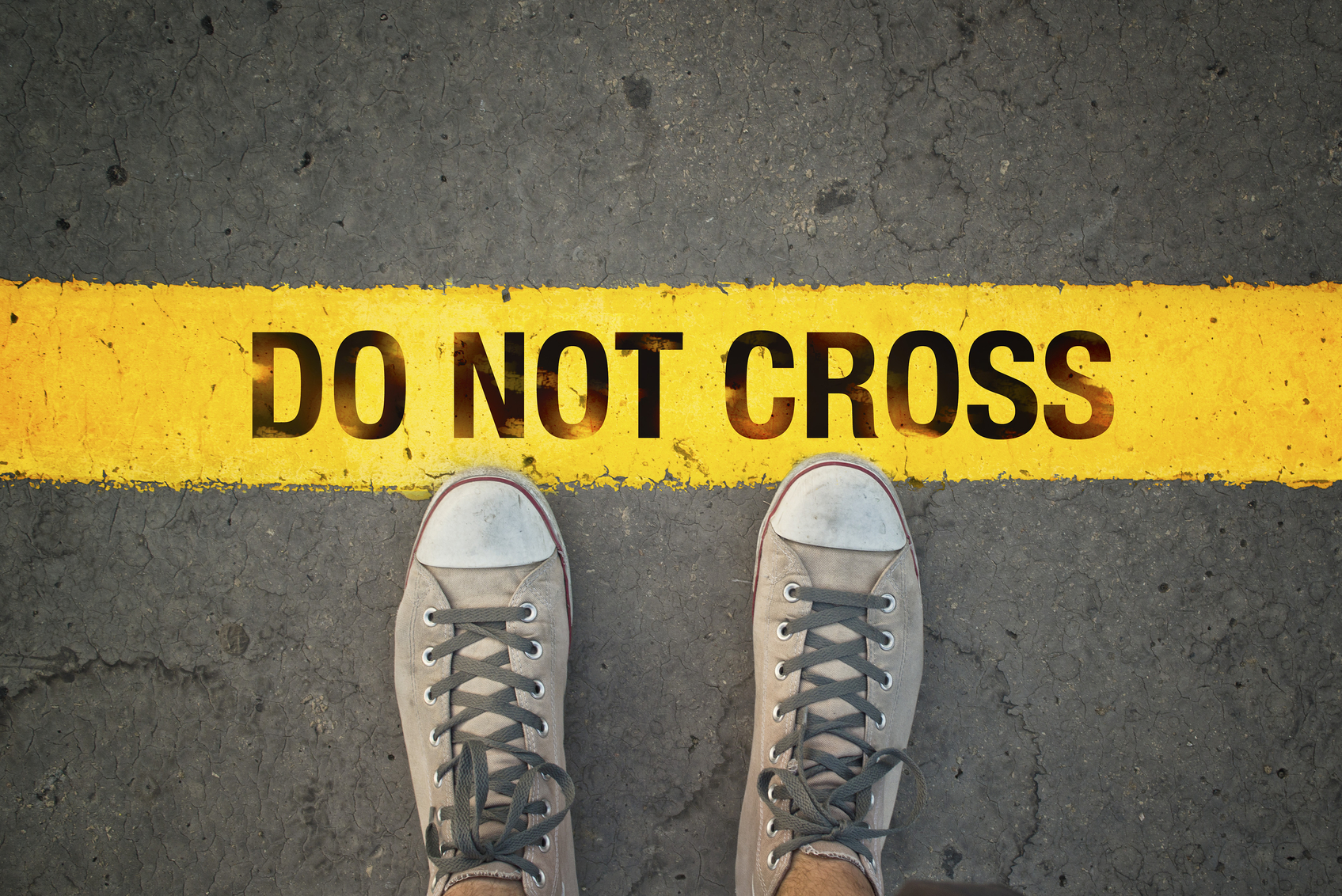 Man in sneakers standing at the yellow line with Do Not cross message